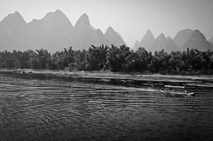 Down the Li. (Nina Matzat) Tags: china morning trees light sea plants reflection water beauty silhouette sunrise river palms boats boot li boat early weed nikon shadows guilin yangshuo hill chinese floating bank surface menschen hills shore dreamy fluss karst landschaft guangxi harvesting carst hgel southernchina sdchina d7000 southnchina