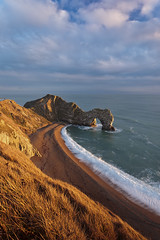 Durdle at Sunset (Joe Rainbow) Tags: ocean winter sea beach water grass landscape coast tide cliffs coastal dorset grasses jurassic durdle durdledoor