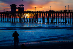 Photographer and the Pier (EthnoScape) Tags: california sunset sky sun reflection tower beach water station silhouette clouds reflections pier waves photographer towers lifeguard oceanside lifeguardtower lifeguards lifeguardstation