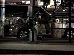 Man Texting at Night Bus Stop 1 (Kojotisko) Tags: night streetphotography brno cc creativecommons czechrepublic streetphoto fujifilmfinepix fujifilmfinepixsl1000 fujifilmfinepixsl1000kojotisko
