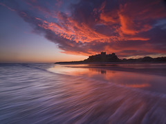 Bamburgh Sunrise (antonyspencer) Tags: ocean uk winter sea england seascape beach sunrise landscape coast dramatic wave northumberland coastline colourful bamburgh bamburghcastle northumberlandcoast