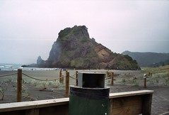 Lion Rock and the rubbish bin view (mikeasaurus) Tags: red sea newzealand summer people brown holiday green rot beach nature water rain strand meer fuji sommer natur 200asa olympus rainy nz bleak grn braun tasmansea raining westcoast downunder piha lionrock rubbishbin trip35 colorfilm aoteoroa almostdeserted december2011