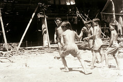 JE28-16-11-1956 (The Ulu and the Museum) Tags: people playing boys buildings river outside others community objects games location clothes daytime subject 1956 date longhouse ethnicity grouppicture baram gasing timeofday westernclothes tinjar longsan kenyah longhouseexterior villageorlonghouse kenyahsebob longloyang