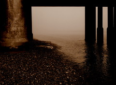 Between pillars (Gareth Priest) Tags: sea mist beach sepia pier surreal eerie pebbles pillars