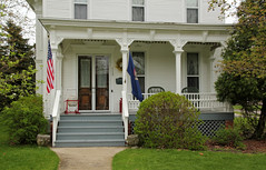 Porch  Hillsdale, Michigan (Pythaglio) Tags: county wood trees house spring doors michigan flag incised caps steps flags double historic sidewalk american porch frame siding residence posts bushes brackets hillsdale triangular dwelling italianate latticework spandrels