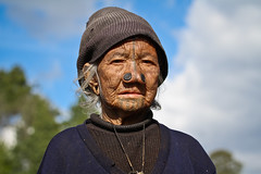 Apatani old woman in the ricefields of Ziro. Arunachal Pradesh, NE India (NeSlaB .) Tags: poverty old travel portrait woman india colors look canon photo women asia village dress indian traditional country culture photojournalism tribal clothes ornaments tradition tribe ethnic society ricefields developingcountries reportage nationalgeographic ethnography neindia ziro ethnies apatani noseplugs neslab davidecomelli