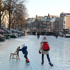 A chair is the time-honored and indispensable skating aid (Bn) Tags: winter people cold holland ice hockey netherlands dutch amsterdam kids geotagged fun frozen chair topf50 downtown iceskating skating joy kinderen nederland freezing first canals age skate stick prinsengracht anton tem