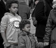 Enchanted brothers. (Bas Tadema) Tags: street portrait bw white black amsterdam square see raw hand looking brothers dam streetphotography portraiture staring portret zwart wit plein firebreather enchanted zien straat broers kijken gekleurd straatfotografie vuurspuwer betoverd starende krullebollen