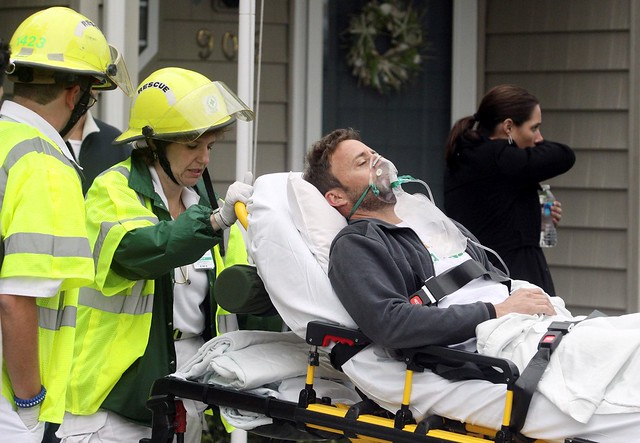 A man is taken away by paramedics at the scene of accident after a U.S. Navy F/A-18D fighter jet crashed into an apartment complex in Virginia Beach April 6, 2012. The Navy fighter crashed soon after take-off into an apartment complex in Virginia on Frida