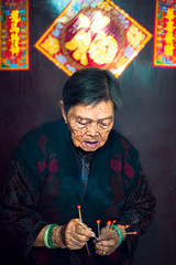 Ancestor Worship (TGKW) Tags: old grandma portrait people woman flower floral fire sticks worship expression smoke religion chinese hong kong tai ancestor jade elderly po gran bangle lit granny cardigan lam incense kun popo 5208