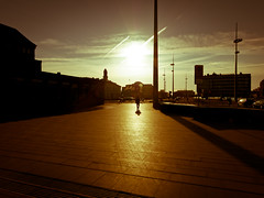 In The Near Future (Rutger Blom) Tags: city sky sun sunlight man clouds walking airplane afternoon shadows traffic silhouettes sidewalk lanterns poles contrails malmö malmo canonpowershots100 5226mm