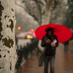 her red umbrella (~mimo~) Tags: china street red tree rain umbrella fence walking photography shanghai bokeh pavement candid trunk odc mimokhair