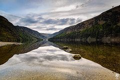 Three Stones... (fearghal breathnach) Tags: longexposure trees ireland lake reflection water vanishingpoint rocks symmetry glendalough valley wicklow cliche clich wicklowmountains leadinglines lae glendaloughlake greystonescameraclub 52weeksof2016