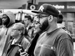 Onlooker (Mac McCreery) Tags: blackandwhite birmingham phone crowd watching baseballcap sigma1770dcmacro pentaxk5iis