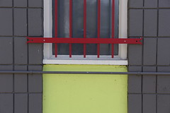 IMG_0258 (Patrick Hanlon) Tags: red window yellow grey bars geometry cinderblock parallel