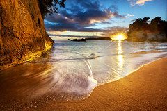 Cathedral Cove Beach Sunrise Starburst - New Zealand (Daniel Peckham) Tags: ocean travel sea newzealand fern beach sunrise cove limestone sunburst coastline ferns coromandel pinnacle seastack cathedralcove oceania coromandelpeninsula