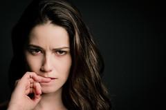 Nailbiting (dawolf-) Tags: girl head annoyed hand nail biting finger hair contrast beautydish canon eos 7d 50mm strobe strobist portfoliofaces recreatethumbs