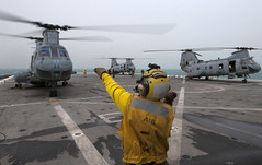 A Sailor signals a helicopter to turn off its engine on the flight deck. (Official U.S. Navy Imagery) Tags: sandiego usnavy underway deployment arabiangulf 11thmeu 5thfleetaor ussneworleans wwwfacebookcomusnavy