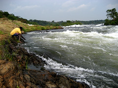 Nile (albinobobman) Tags: africa boy man water yellow river outdoors rocks stream waves earth african nile uganda splashes