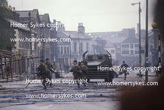 HUMBER 1 TON (PIG) 'FLYING PIG' PATROLS THE STREET OF BELFAST THE TROUBLES PHOTO BRITISH ARMY SOLDIERS RIOTS NORTHERN IRELAND  1980S UK (Homer Sykes) Tags: uk ireland army riot rifle belfast soldiers northernireland guns british 1980 society 1980s gbr fallsroad thetroubles archivestock