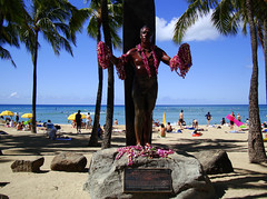 DSC02433 (prietke) Tags: ocean flowers trees beach sign statue clouds hawaii coast sand rocks waves unitedstates pacific waikiki oahu tourists lei palmtrees pacificocean hawaiian hi honolulu waikikibeach umbrellas kuhio dukekahanamoku hawaiianislands dukekahanamokustatue kuhiobeach kuhiobeachpark