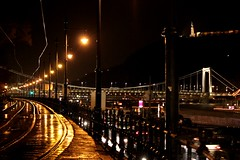 """""""Dive again and again into the river of uncertainty. Create in the dark, only then can you recognize the light.""""  Jyrki Vainonen (♪ fotodisignorina ♪ Felicia Violi PHOTOGRAPHY) Tags: bridge rain night digital canon river photography eos reflex hungary nightshot streetlamps budapest tram danube"""