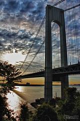 V-ZBridgeSunrise2 (JVierno77) Tags: ocean bridge light shadow sea sky sun ny newyork water brooklyn clouds photoshop sunrise canon rebel bay glow view cross suspension column 1855mm statenisland hdr narrows t3i verrazano vz fortwadsworth cs5 vznarrowsbridge