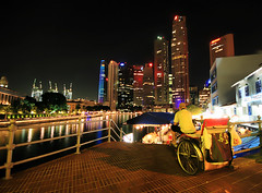 Big City Lights in Singapore (` Toshio ') Tags: road city trees man reflection water architecture night buildings harbor singapore cityscape traffic restaurants freeway cbd rickshaw hdr highdynamicrange boatquay centralbusinessdistrict toshio
