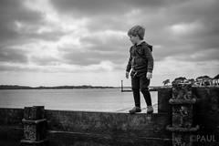 Boy on the beach (PaulGibsonPhoto) Tags: boy england sky bw beach mono coast seaside fuji child play south son dorset fujifilm groyne poole x100s