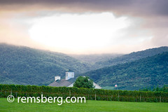 View of vineyard and mountains in winery in Virginia (Remsberg Photos) Tags: trees usa sunlight mountain storm landscape outdoors virginia wine drink farm whitehouse winery rows valley grapes hillside rollinghills vinyard crozet sunthroughclouds alcoholicdrink outdoorsthings