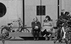 Our lips are sealed. (Bas Tadema) Tags: street door portrait blackandwhite bw amsterdam bench square mond dam pigeon dove bikes lips blondie talking portret zwart wit plein fietsen meisjes vogel twee deur vrouwen dames straat sealed bankje duif lippen zwijgen dicht verzegeld