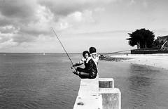 Fishing (lepetitguillaume) Tags: friends sea blackandwhite bw sun fish france film analog 35mm pier blackwhite seaside spring fishing nikon flickr friendship kodak britain tmax jetty bretagne nb 135 launch fm chill fm2 jete noirblanc fishingrod