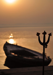 Varanasi (Bhaskar Dutta) Tags: orange india flower water silhouette sunrise river boat varanasi hue trishul trident