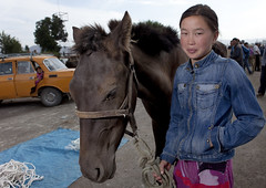 Young Woman Holding A Horse At The Animal Market Of Kochkor, Kyrgyzstan (Eric Lafforgue) Tags: people horse woman smile smiling animal horizontal female standing mammal person one asia exterior market marketplace centralasia kyrgyzstan humanbeing oneperson colorphoto animalmarket bridle kochkor kyrgyzrepublic kirghizistan kirgistan lookingatcamera 1186 waistup kirghizstan kirgisistan    quirguizisto