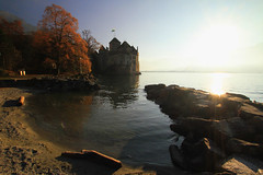 Chillon Castle at Sunset on Lake Geneva (` Toshio ') Tags: autumn sunset lake tree castle history fall beach switzerland sand rocks europe european 7d chillon lakegeneva lacleman toshio chilloncastle