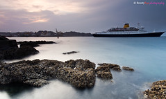 Muscat - Low Tide at the Port (Beauty Eye) Tags: city longexposure nightphotography sunset sea mountain seascape building green eye architecture night photoshop canon dark landscape boats eos rebel landscapes long exposure day seascapes nightshot outdoor royal scene adobe bluehour om tamron oman muscat souq royale 2012 lightroom t3i mct mutrah matrah cameraraw parisopera ultrawideangle   f3545 600d    beautyeye masqat 1024mm   canon600d  sultanqaboosport tamronspaf1024mmf3545diiild rebelt3i kissx5 diiild canon600deos oman omanomancountry tamronspaf1024mmf3545d muscatsultanqabooscornich omanevents