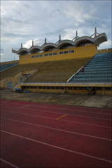 hue-6143-ps-w (pw-pix) Tags: grandstand seats blue red yellow white lines lanes marking track surface rubber rubberised olympicrings olympicsymbol stadium sports sportsstadium decayed dilapidated weathered timecapsule interesting wonderful afternoon lateafternoon cloud clouds cloudy overcast dull green grey soccer pitch trackandfield running hurdles steeplechase concrete grass