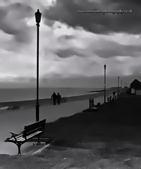 Walking Under A Moody Sky, Hythe. (ziggystardust111) Tags: sea sky people art beach water grass lines silhouette clouds bench kent lamps simple tones hythe shepway 450d canon450d wwwvincewinterphotographycouk