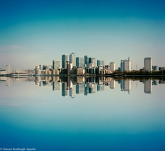 Canary Wharf Skyline - London Reflection (Original Version) (Simon & His Camera) Tags: city blue sky urban reflection building london tower water thames skyline architecture skyscraper river landscape island office waterfront outdoor horizon symmetry canarywharf iconic simonandhiscamera