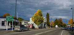 Intensity of light (Jocey K) Tags: street autumn trees newzealand sky signs cars clouds buildings town shadows southisland geraldine logos archtiecture southcanterbury tripdownsouth