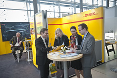 Delegates study information leaflets at the DHL exhibition stand