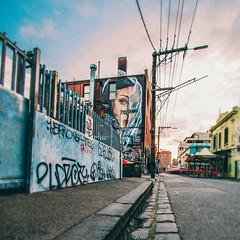 love this neighbourhood. (lucidddreamin') Tags: street sky urban streetart clouds puddle graffiti mural colours fitzroy australia melbourne tags goldenhour argylestreet