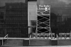 FX301026-1-2 The Body Extended (Lawrence Holmes.) Tags: street uk blackandwhite tower sign poster fuji leeds streetphotography scaffold juxtaposition x30 hivis henrymooreinstituteleedsuk lawrenceholmes