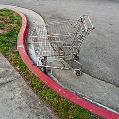 My Ticket Home (i(saw) e(saw)) Tags: street red green grass concrete curves shoppingcart minimal sidewalk squareformat walkabout lookingdown minimalism simple curb 2012 panasoniclx3