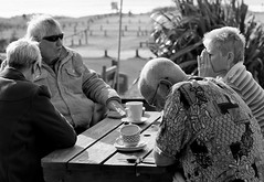 Not that shirt again (farwest56) Tags: uk england people bw holiday man cup sunglasses table 50mm cafe women couple cornwall sony tourists carpark alfresco gwithian stivesbay a350 sal50f14