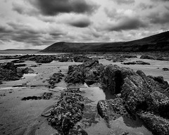 Beach at Manorbier, Pembrokeshire (ammgramm) Tags: uk sky bw beach water wales clouds blackwhite sand rocks naturallight pembrokeshire manorbier headland 1755mm d300s silverefexpro2