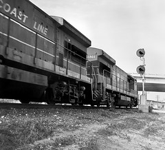 SCL GE U36B locomotives lead a TOFC freight train westbound through the diamond on the former ACL mainline at Auburndale, Florida, 1970's (alcomike43) Tags: old railroad blackandwhite bw classic vintage ties photo diesel tracks engine trains historic negative photograph rails locomotive freighttrains ge acl ballast rightofway scl dieselengine mainline 1828 seaboardcoastline us92 diesellocomotive highwayoverpass u36b raodbed tofc dieselelectriclocomotive atlanticcoastline blocksignal auburndaleflorida conventionaljointedsectionrail diamondprotectionblocksignal