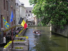 In Bruges (andyscho2004) Tags: flowers tree 2004 water buildings boat canal spring europe belgium eu olympus flags tourists bruges railing c750uz