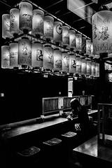 . (robbie ...) Tags: ricoh gr 28mm osaka japan girl sitting restaurant eating japanese writing letters lanterns chopsticks stool food black white monochrome mono bw