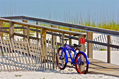 Beach Cruiser (Hall Photographia) Tags: blue red tourism beach bicycle fence sand colorful purple bright florida violet boardwalk whitesand pensacola pensacolabeach seventeen beachcruiser floridatourism pensacolabeachflorida beachcruiserbicycle vacationlocations hallphotographia